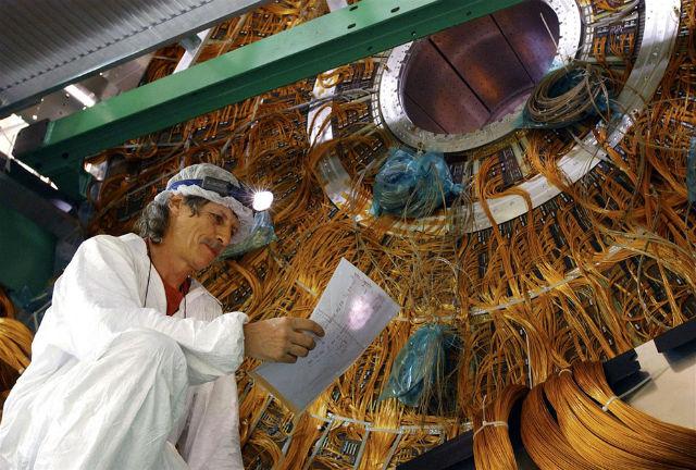 Август 2013 года, техник соединяет провода внутри экспериментальной устновки ATLAS. Нельзя ошибиться ни с одним, иначе результат запутает физиков (фото Maximilien Brice/CERN).
